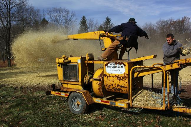 ANDREW LEIBENGUTH/TIMES NEWS A crew from Northeast Hydroseeding and Landscaping Inc. blows hay on the new field. The materials and services were donated by owner Wayne Postupack.