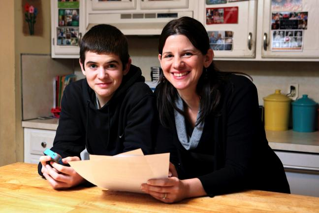 AP Photo/Michael Dwyer Janell Burley Hofmann, right, holds a copy of the contract she drafted and that her son Gregory, left, signed as a condition for receiving his first Apple iPhone.