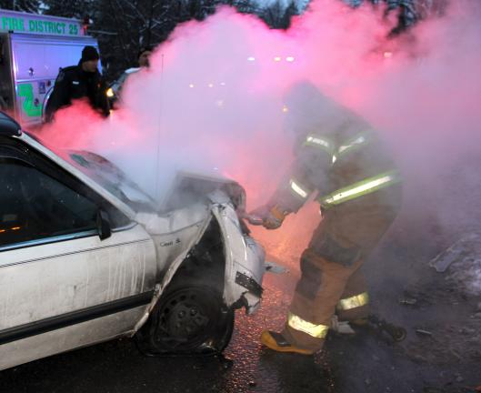 ANDREW LEIBENGUTH/TIMES NEWS A firefighter sprays water into the smoke-filled engine compartment.