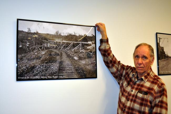"DONALD R. SERFASS/TIMES NEWS Harry Miller, president, Summit Hill Historical Society, points out a framed image in the town's borough building that depicts extensive workings geared toward extinguishing an underground fire at what was called the ""$3…"