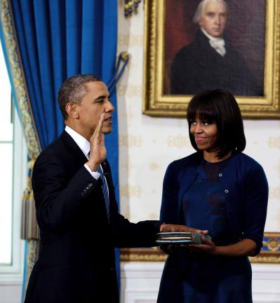 AP PHOTO President Barack Obama is officially sworn-in by Chief Justice John Roberts, not pictured, in the Blue Room of the White House Sunday, in Washington, as first lady Michelle Obama holds the Robinson Family Bible.