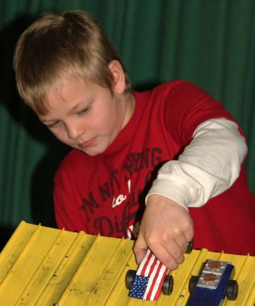 ANDREW LEIBENGUTH/TIMES NEWS Robert J. Frederick, 8, son of Robert W. and Missy Frederick, places his patriotic car on the track.