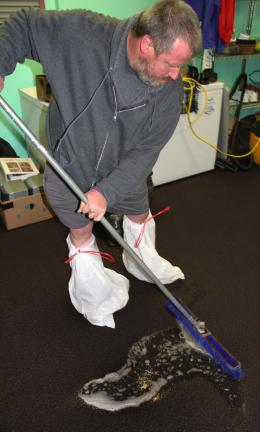ANDREW LEIBENGUTH/TIMES NEWS Above, Tongue wears garbage bags on his feet as he squeegees water out of the carpet.