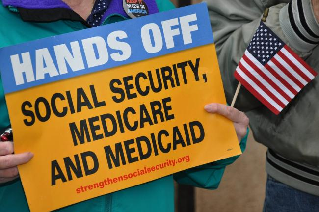 AMY MILLER/TIMES NEWS A member of the rally holds a sign and American flag on Wednesday in the hopes of raising awareness of the proposed cuts to Social Security, Medicare and Medicaid.