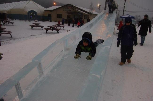 TERRY AHNER/TIMES NEWS Zane Fatzinger, 4, of Palmerton, glides down this life-size sliding board ice carving that could be enjoyed at the Winter Festival held this past weekend at Blue Mountain Ski Area.