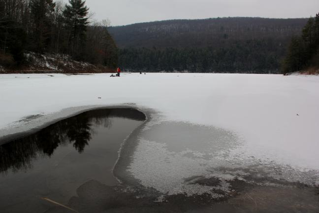 A thin layer of ice sits along the outer bank and inlet waters of the Tuscarora Lake Tuesday afternoon. Ice fisherman state the average ice thickness of the lake was 7 inches, adding that 4 inches are higher are safe to walk on.