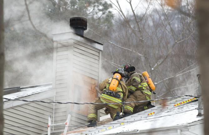 BOB FORD/TIMES NEWS Firefighters concentrate on the chimney area as they battle a house fire along the Lentz Trail in Jim Thorpe yesterday.