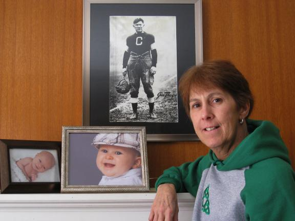 SPECIAL TO THE TIMES NEWS Peggy Sue O'Donnell, grand marshal of the 2013 St. Patty's Day Parade, stands near photos of her grandson, Cadden (with hat), and her great-nephew, Carter Reis, with a photo of All American Jim Thorpe in background.