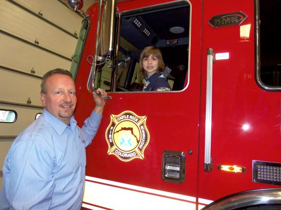 As members of Cub Scout Pack 160 of Clark Summit tour the KME facilities in Nesquehoning, Cub Scout John Paul Shields enjoys sitting in a soon to be delivered Colorado fire truck under the watchful eye of KME sales manager Mark Kopunek.