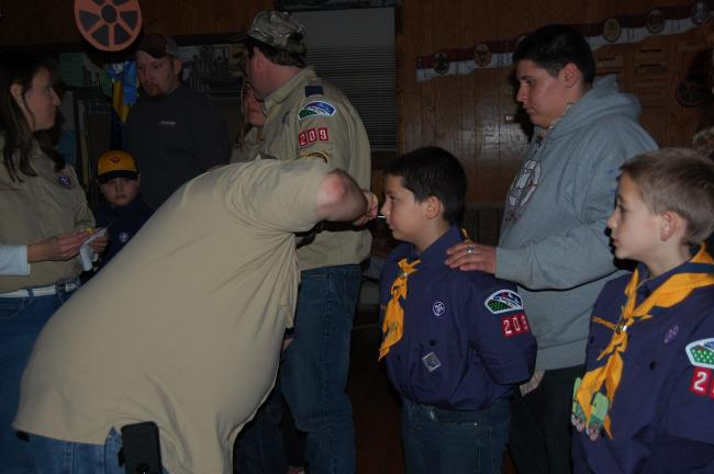 Hugo Marin receives the mark of the Wolf from Assistant Scoutmaster Scott Long. With him is his brother Henry Marin.