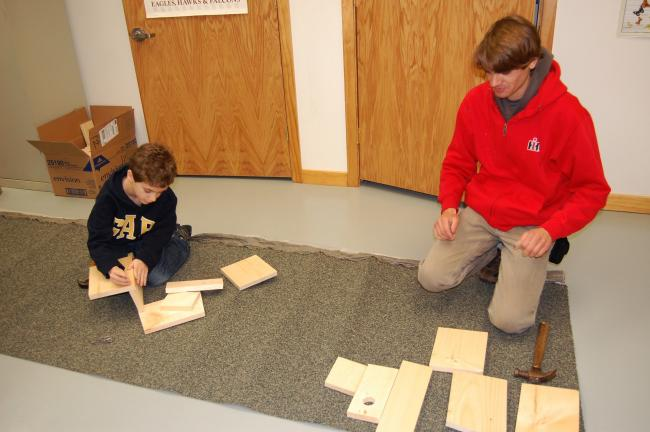 Aiden Sell and Joseph Zerecie spread the boards that will make a birdhouse.