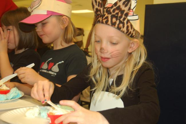 TERRY AHNER/TIMES NEWS Parkside Education Center kindergarten pupils Paige Kresge, 6, and Shea Shollenberger, 5, concentrate as they decorate their cupcakes as part of an activity geared toward Read Across America Week.