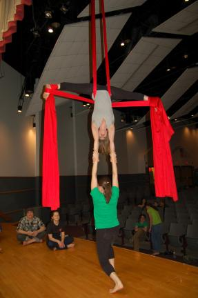 Laura Ernst of Des Moines, Iowa, hangs upside down on the aerial silks while holding a student with her hands.