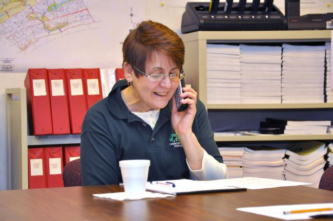 AMY MILLER/TIMES NEWS Jackie Nalesnik, a Carbon County resident and volunteer EOC staff member, makes a telephone call to a school to inform them that the severe weather emergency exercise is completed and they can resume daily operations.