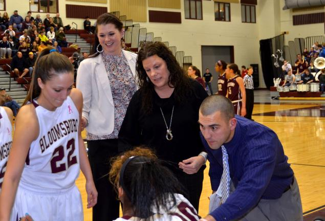Bloomsburg assistant coach Diane Decker and volunteer assistants Chris Decker and Rachel Connely talk with the team during a timeout. All three are former basketball standouts at Marian Catholic High School.