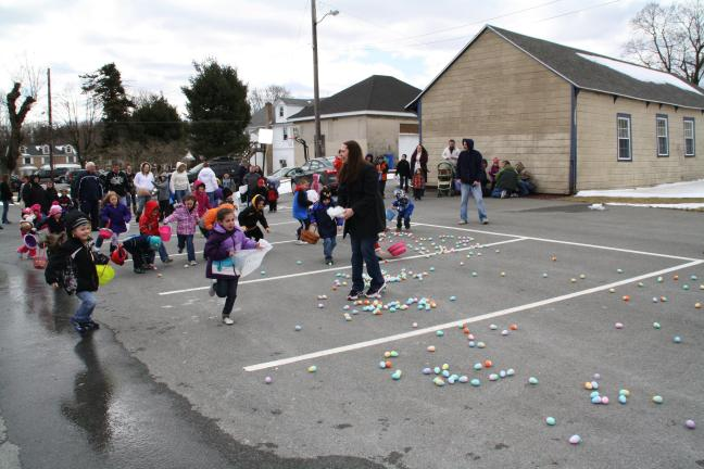 KATIE WARGO/SPECIAL TO THE TIMES NEWS Summit Hill youngsters scramble across the parking lot next to the Hilltop Community Center in the borough to gather eggs during the town's annual easter egg hunt which included over 1000 eggs, lots of prizes…