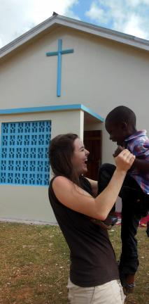 SPECIAL TO THE TIMES NEWS Misericordia University occupational therapy student Debbie Keys of Jim Thorpe, enjoys a playful moment with a child outside St. Joseph's Church in Jamaica.