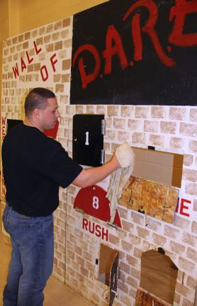 ANDREW LEIBENGUTH/TIMES NEWS Jason Lorah, a DARE coach and West Penn Township Police officer, volunteers his time cleaning the D.A.R.E. wall after the event last month in Tamaqua.