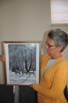 LINDA KOEHLER/TIMES NEWS Diane Danielson, Palmerton Area Library director, holds a black and white photograph, featuring a winter scene of the park in Palmerton, that Connie Rinehart is entering in the upcoming Sixth Annual Photography Show to take…