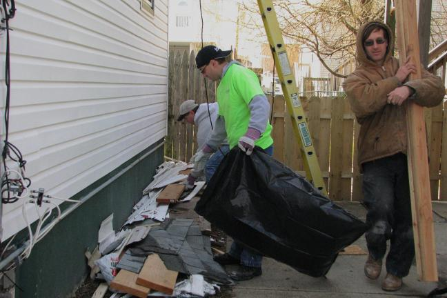 KEITH HOUSE/SPECIAL TO THE TIMES NEWS Eric Nothstein picks up debris as Pastor Greg Laible waits with a trash bag. Bruce Snyder carries a piece of lumber. The crew also made repairs outside, such as cleaning up debris, rebuilding fences and…