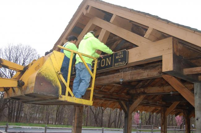TERRY AHNER/TIMES NEWS  Slatington Borough Crew workers erect a replica railroad station sign on the pavilion at the Slatington Trailhead Tuesday morning.