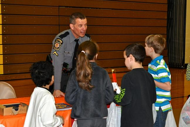 VICTOR IZZO/SPECIAL TO THE TIMES NEWS Students from Mrs. Fedorko's 1st grade class speak with Trooper David Peters, a Community Service Officer with the Pennsylvania State Police during the Weatherly Wellness Fair that was held in the Weatherly…