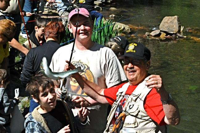 Panther Valley students Brandon Velez (left) and Evan Wooding (center) look on as Palmerton Legion Post 269 volunteer Louie Moyer helps retrieve the rainbow trout they caught during last year's annual Carbon County Kids Fishing Derby.