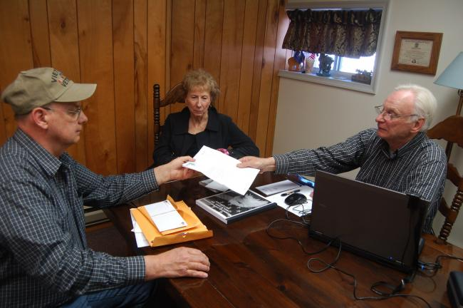 TERRY AHNER/TIMES NEWS Vietnam veteran Barry Jones (front), of Slatington, hands his paperwork over to Frederick Smith, a veterans outreach specialist from the American Legion in Wilkes-Barre, as state Rep. Julie Harhart (R-Lehigh/Northampton)…
