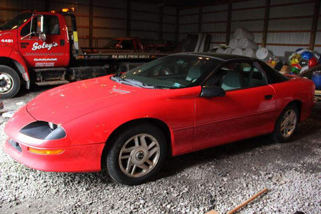 ANDREW LEIBENGUTH/TIMES NEWS A 1995 Chevy Camaro sits in a bay at Soley's Garage in West Penn after it's driver led police on a 10-mile chase before being stopped in Blythe Township by state police. West Penn Police spent time today documenting all…