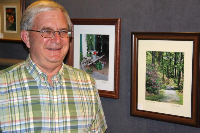 ANDREW LEIBENGUTH/TIMES NEWS Photograph artist Dale Traupman with some of his work currently on display at Stonehedge Gardens in South Tamaqua.