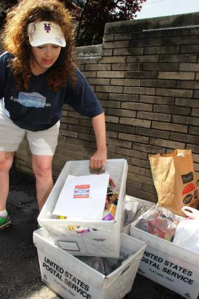ANDREW LEIBENGUTH/TIMES NEWS United States postal carrier Lisa Green, of West Penn, unloads many cartons of donated food from her truck Saturday to the Trinity Food Pantry. Green has been the key coordinator for the Stamp Out Hunger campaign in…