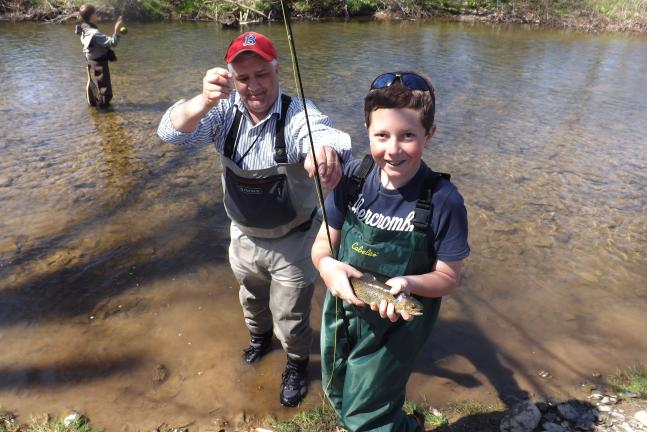 MICHAEL A. HEERY/SPECIAL TO THE TIMES NEWS Sam Maholick (right) proudly displays the 14-inch trout that he reeled in during the recent Lehighton Area Middle School Fly Fishing Club field trip to Baer Memorial Park in Lehighton. Helping Maholick with…