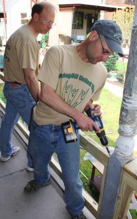 ANDREW LEIBENGUTH/TIMES NEWS Participating in the Schuylkill United Way's Day of Caring, Air Products employees plant superintendent Eric Dreyfus, of Andreas, and electrician Gary Clemson, of West Penn, work to replace old railing located on the…