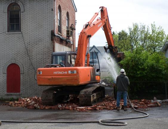 BOB FORD/TIMES NEWS Workers begin to demolish a small building at the rear of American Fire Co. No. 1, Lansford.