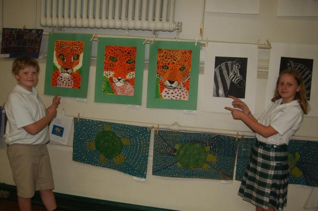 TERRY AHNER/TIMES NEWS St. John Neumann Regional School fifth-graders Timothy Hillabrand and Erica Messics proudly display some of the art work that was on display recently at its annual art show at the Palmerton campus.