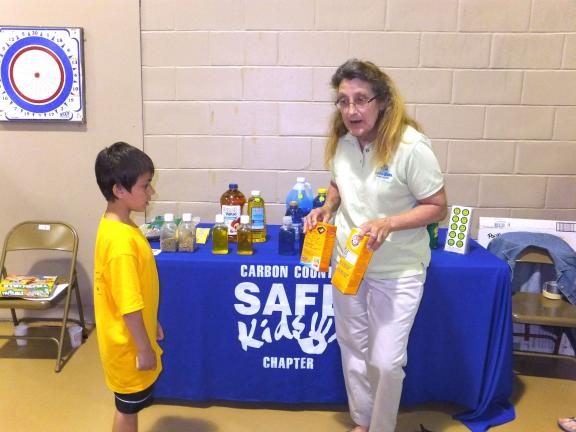 Stacey Solt/TIMES NEWS Mindy Graver, chairperson of Carbon County Safe Kids, asks Nicholas Zeigenfuss and his classmates if they can tell the difference between Arm & Hammer baking soda and carpet cleaner, showing them only the back of the package…