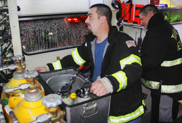 ANDREW LEIBENGUTH/TIMES NEWS Tamaqua Rescue Squad members Captain Matt Hill and Nathan Bowman, right, fill oxygen tanks for firefighters.