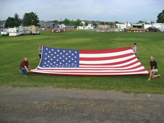 Members of the Summit Hill Lions Club display a massive American flag that will fly in Ludlow Park on holidays and will be part of a seasonal flag program to recognize Summit Hill resident and former residents. Holding the flag are Joseph O'Gurek…