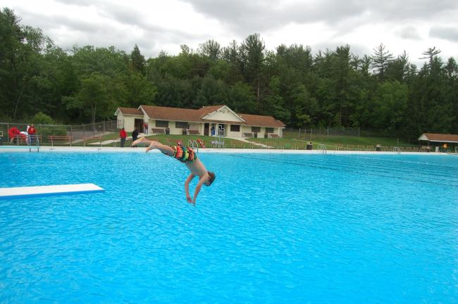 TERRY AHNER/TIMES NEWS Justin Sebelin, 7, of Palmerton, shows off his form as he jumps off one of the new diving boards at the Palmerton Memorial Pool, which opened for its 67th season this past Saturday.