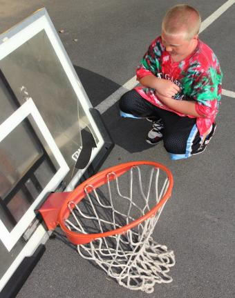 ANDREW LEIBENGUTH/TIMES NEWS Upset that he can't play basketball, Geno Turner, 8, looks over vandalism done to a baskeball hoop at the South Ward playground. Both hoops were taken down temporarily to prevent future vandalism and until repairs are made.