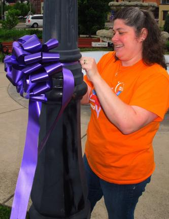 ANDREW LEIBENGUTH/TIMES NEWS  Volunteer Rosalee Rehrig, of West Penn, places a purple ribbon on one of the lights located at the Depot Square Park.