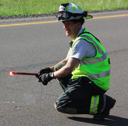 ANDREW LEIBENGUTH/TIMES NEWS Helping out at oil spill Tresckow Fire Chief Joe Geusic places road flares along the northbound lanes of Interstate 81 to limit traffic to one lane as crews clean up a quarter-mile chemical spill.