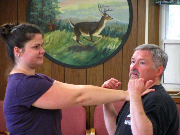 CAJETAN BERGER/SPECIAL TO THE TIMES NEWS Lynette Silva mock chokes second-degree black belt and martial arts teacher, Gary Guldin, as he instructs a self-defense lesson at the Ontelaunee Rod and Gun Club as part of the National Wild Turkey…