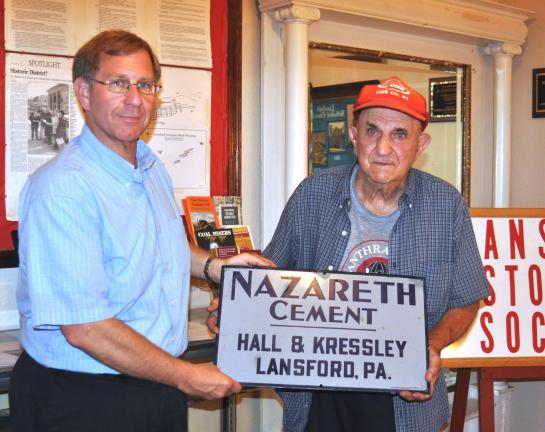 DONALD R. SERFASS/TIMES NEWS  Bill Harleman, left, president of the Lansford Historical Society, thanks Michael Knies for donating an enameled sign. Knies, who will turn 92 this year, has safeguarded the sign for nearly eight decades.