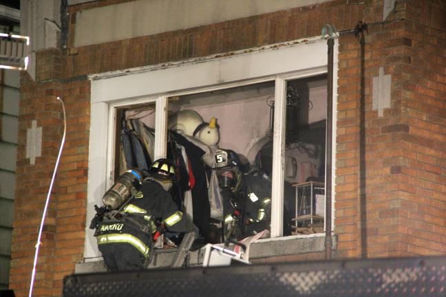 ANDREW LEIBENGUTH/TIMES NEWS Firefighters remove flammable items from the second floor to the home.