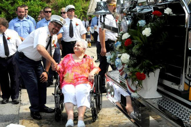 Ron Gower/TIMES NEWS Nesquehoning Fire Chief John McArdle and borough resident Ann Fauzio take part in christening new 103-foot ladder truck which was dedicated by Nesquehoning Hose Company No. 1 on Saturday.
