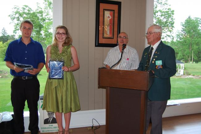 ELSA KERSCHNER/TIMES NEWS Kyle Cope and Elisha Kistler receive scholarships from Larry Engle, far right, as Lion Pres. William Ravert watches.