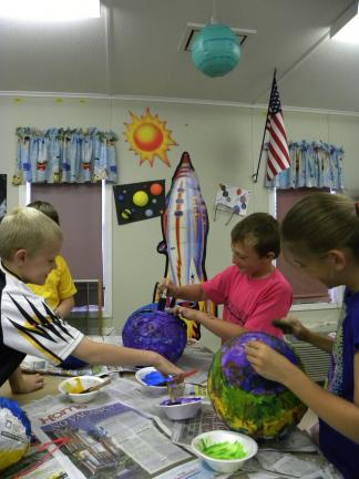 DANIELLE FOX/TIMES NEWS Fourth grade students, L-R, Devin Schlier, Brielle Gosselin and Wyatt Mumich decorate papier-m'ché planets while they learn about the solar system.
