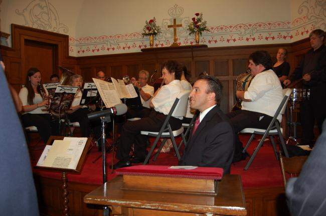 Jason Breidinger, master of ceremonies, stands before the Northern Lehigh Community Band during July 4 Heritage Day program at the Slatington Baptist Church.