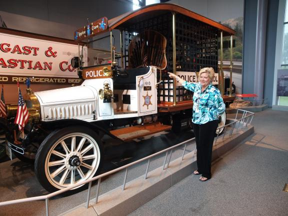 "AL ZAGOFSKY/SPECIAL TO THE TIMES NEWS Sheryl Hawk, director of development at America On Wheels points to a display of Billy clubs on a 1916 Mack ""Paddy Wagon,"" converted from a former Mack fire truck."